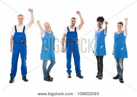 Happy Multiethnic Janitors Standing With Arms Raised