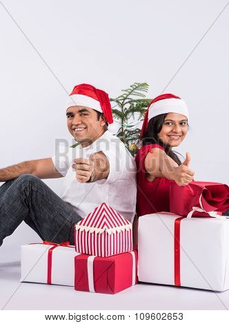 young indian couple sitting with with christmas gifts showing card, asian couple and christmas gift,