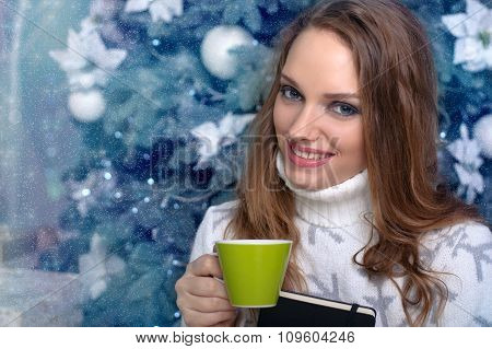 Girl Holding A Book And Drinking A Warm Drink