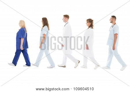 Side View Of Medical Professionals Walking In Row