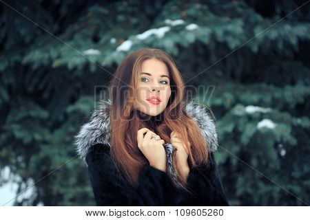 beautiful smiling girl on background of snowy trees. Winter portrait. coat with a hood