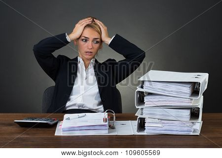 Tired Businesswoman With Hands On Head At Desk