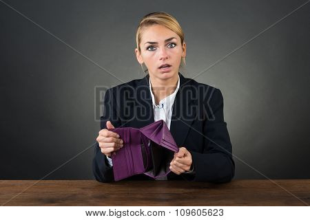 Businesswoman Showing Empty Clutch At Desk