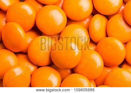 Close Up On Pile Orange Milk Chocolate Candies Crisp Shell