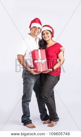 young indian couple smiling with with christmas gift, asian couple and christmas gift, with santa ha