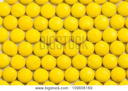 Close Up Neatly Arranged Yellow Milk Chocolate Candies Crisp Shell