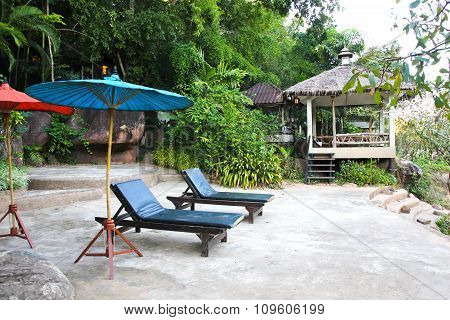 Two Empty Chairs Under Umbrella On River In Thailand