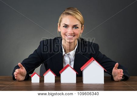 Businesswoman With Model Houses Arranged In Graph Order