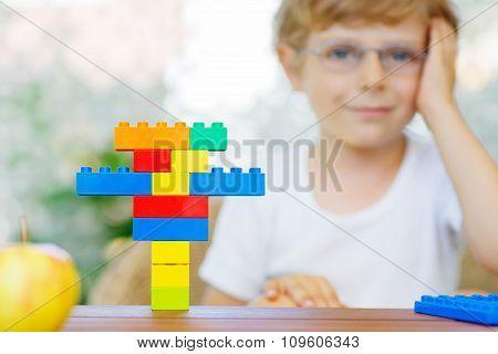 Little kid boy playing with plastic blocks