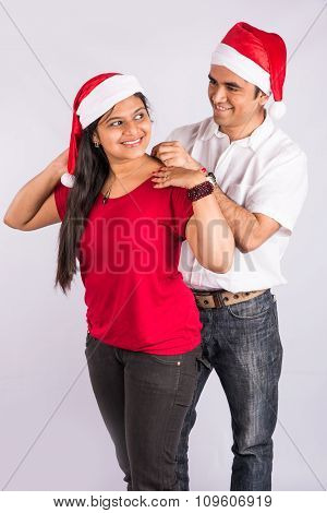 Man placing necklace on woman's neck in christmas time, indian man gifting necklace to wife of girlf