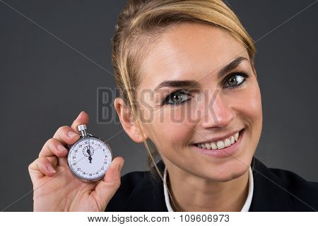 Businesswoman Showing Stopwatch Over Gray Background