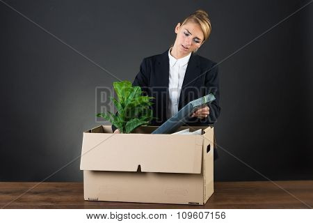 Sad Businesswoman Packing Her Belongings At Desk