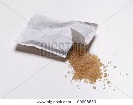 Opened brown sugar bag isolated on White background.