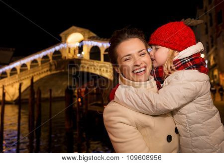 Daughter Kissing Mother Near Rialto Bridge In Christmas Venice