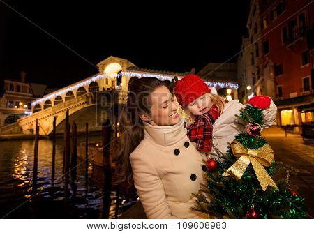 Happy Mother And Daughter In Venice Looking On Christmas Tree