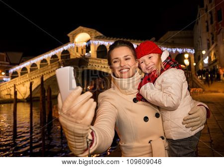 Mother And Daughter Taking Selfie With Smartphone In Venice