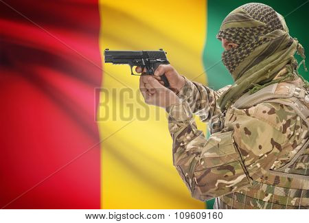 Male In Muslim Keffiyeh With Gun In Hand And National Flag On Background - Guinea