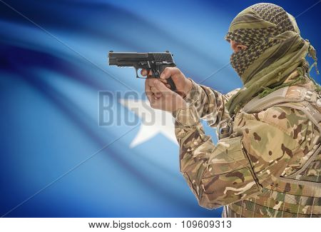 Male In Muslim Keffiyeh With Gun In Hand And National Flag On Background - Somalia
