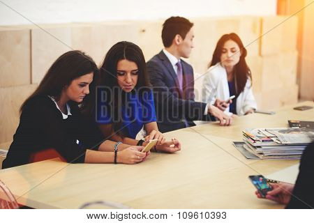 International students using mobile phones during break between lectures