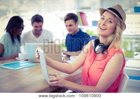 Smiling creative businesswoman working with co-workers in casual office