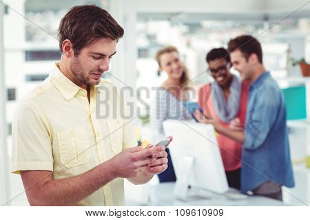 Creative businessman using smartphone in front of colleagues in casual office