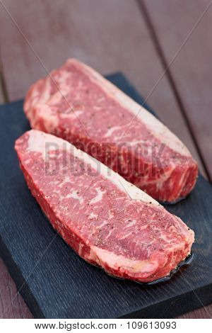 Two pieces of raw striploin steak on wooden plank