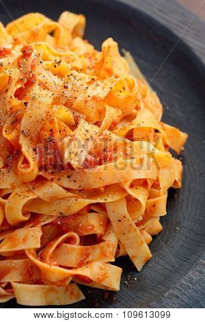 Tagliatelle with tomato sauce in the wooden plate