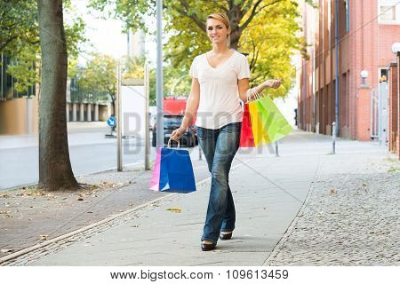 Happy Woman Carrying Shopping Bags On Sidewalk