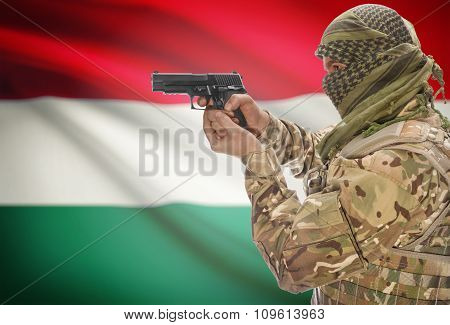 Male In Muslim Keffiyeh With Gun In Hand And National Flag On Background - Hungary