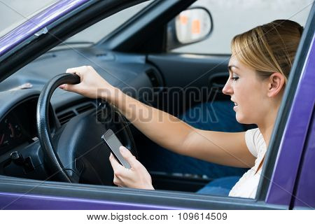 Woman Using Cell Phone While Driving Car