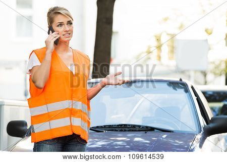 Woman Using Mobile Phone With Broken Down Car On Street