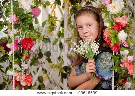 Girl sits on a swing in flower arbor