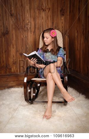The girl in ancient rocking-chair reads the book