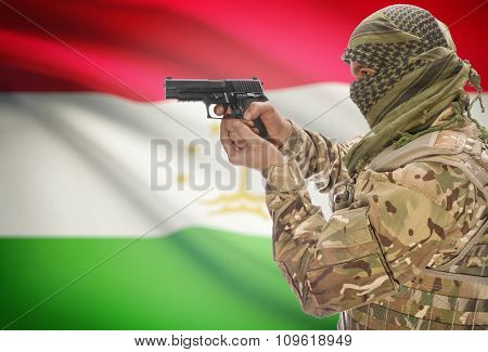 Male In Muslim Keffiyeh With Gun In Hand And National Flag On Background - Tajikistan
