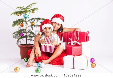 indian kids in christmas time, indian boy sitting in elder sister's lap, santa hat, christmas and in