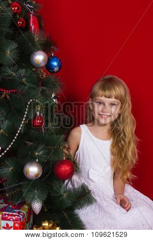 Beautiful baby gir near the Christmas tree in New Year's Eve