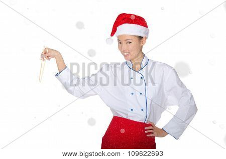 Contented Asian Chef In Christmas Outfit With Chopsticks Under Snow