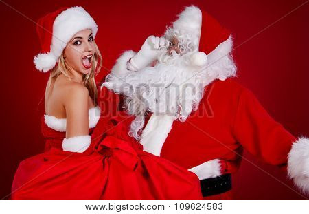 Portrait of happy Santa Claus at red studio  with his woman helper