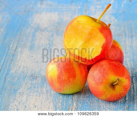 Four Red Apples,bite  On Blue Wooden Floor.