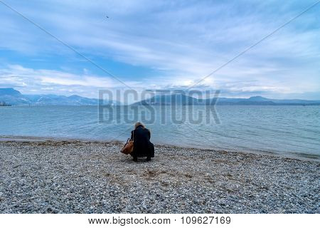Tourist On Beach With Cloudy Sky In Sirmione