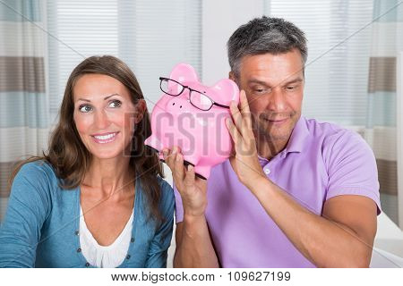 Man And Woman Listening Sound Of Coins In Piggybank