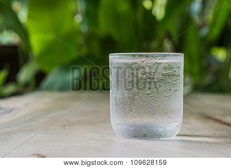 Glass Cold Water On Wooden Floor.