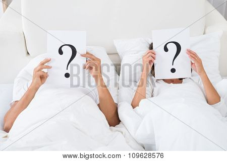 Couple Holding Question Mark Over Faces