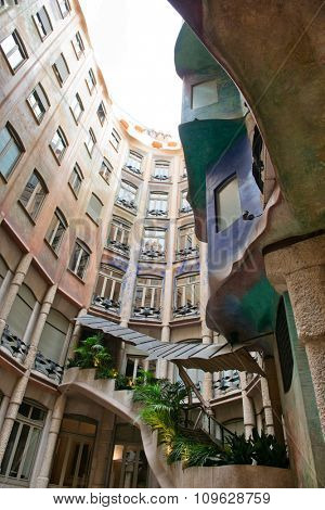 BARCELONA, SPAIN - MAY 01: Low Angle View of Interior Courtyard, Looking Up at Blue Sky from Inside Casa Mila, Barcelona, Spain. May 01, 2015.