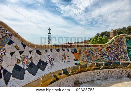 BARCELONA, SPAIN - MAY 01: Detail of a mosaic wall with colorful inlaid ceramic tiles on the main terrace, Parc Guell, Barcelona, Spain, designed by Antoni Gaudi. May 01, 2015