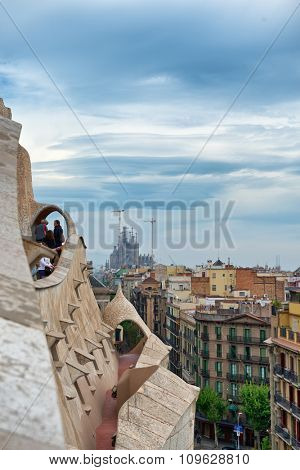 Antoni Gaudi Architecture - View of Sagrada Familia Church in Distance Under Storm Clouds as seen from Rooftop of Casa Mila in Barcelona, Spain. May 01, 2015