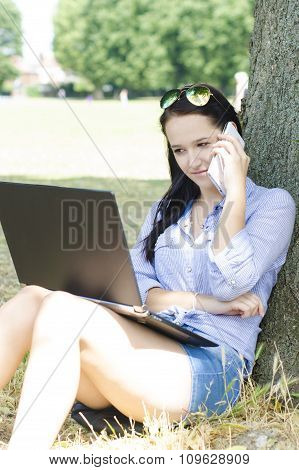 Woman makes a call and has a notebook on a leg in a park
