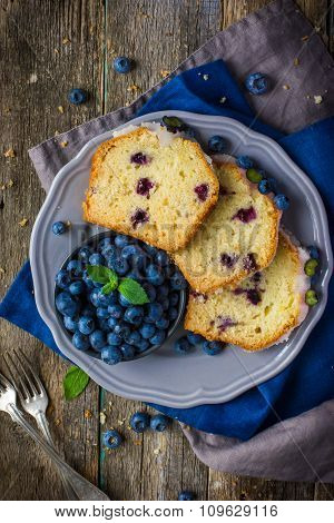 Three Slices Of Blueberry Cake With Sugar Icing And Fresh Berries On Plate