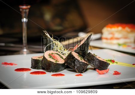 Sushi rolls with salmon and seaweed served on plate