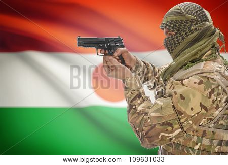 Male With Gun In Hand And National Flag On Background - Niger